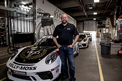 General Manager Andy Kilcoyne with Kelly-Moss's Porsche race cars under new LED lights.